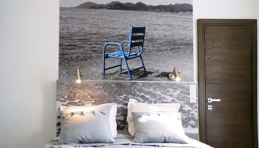 Photo chaise bleue au-dessus d'un lit king size appartement Cannes - Villa Marceau