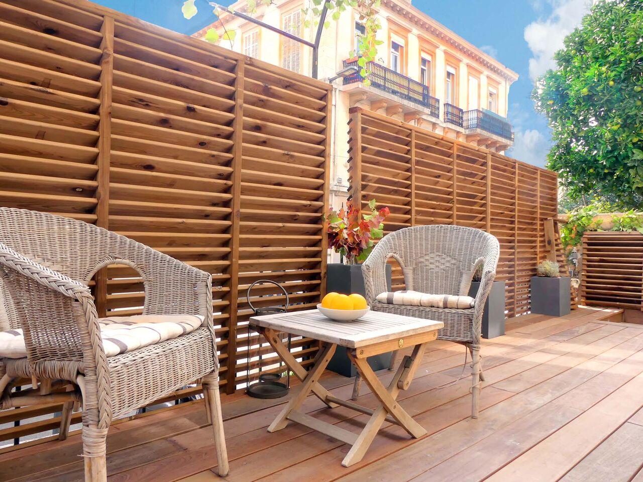 Fauteuils en osier sur terrasse en bois - Villa Marceau